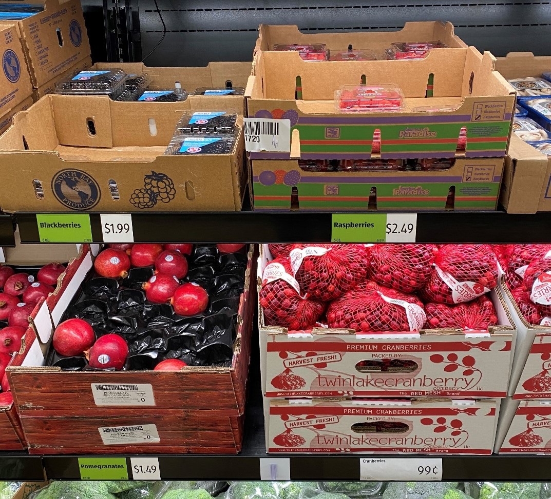 Cranberries, which are considered rarely consumed raw, can be seen displayed here on a grocery store shelf among pomegranates and berries, fresh produce commodities.